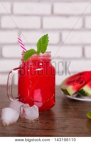 Blended red fruit smoothie in glass jar with straw, ice pieces. Watermelon slices on tha plate. Selective focus. Harvest Concept.