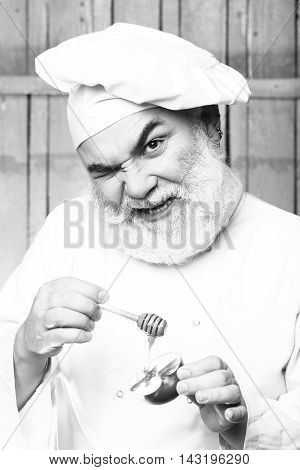 Bearded man cook in chef hat with apple and honey on wooden background black and white
