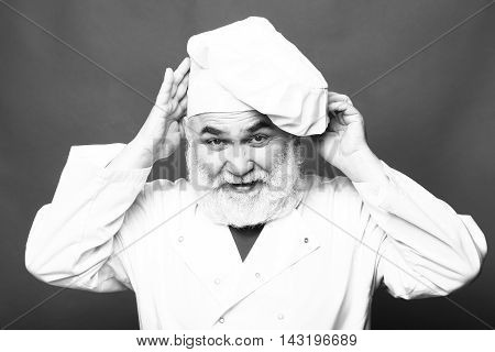 Bearded man cook in chef hat closeup in studio black and white