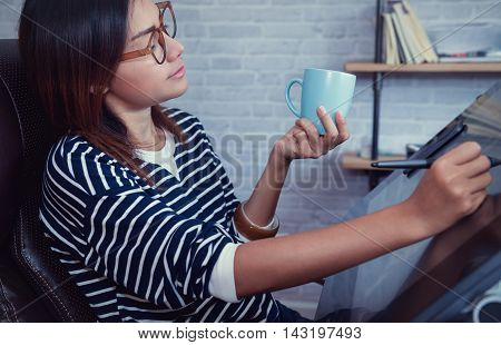 Asian woman looking down on a cup of coffee to sketch focus on face