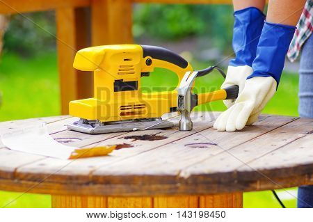 electric sander over a table next to sanderpaper and a hammer