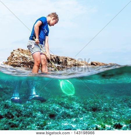 young boy fishing in the sea with a fishing net, near rocks