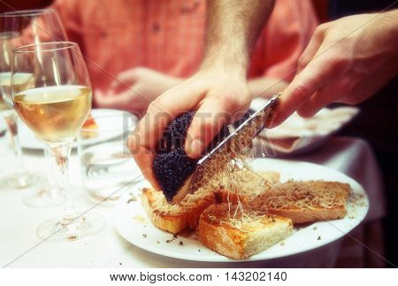 Waiter is grating black truffle on bread with olive oil, toned image