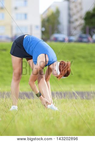 Young Red Haired Ginger Caucasian Female in Athletic Sportgear Having Arms Stretching Excercises Combined with Trunk Bending Outdoors.Vertical Image