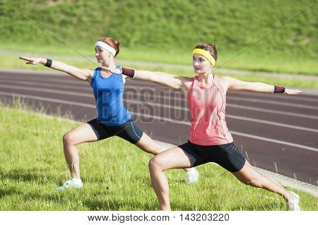 Healthy Lifestyle Ideas and Concepts. Two Young Caucasian Girlfriends in Athletic Sportswear Having Arms Stretching Exercises. Horizontal Image Composition
