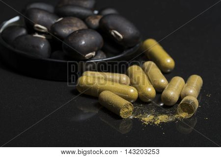 Pill capsule that contain herbal medicine powder of mucuna pruriens seed with blurred of velvet bean seed at the blackground Mucuna pruriens seed have been used for traditional medicine selective focused