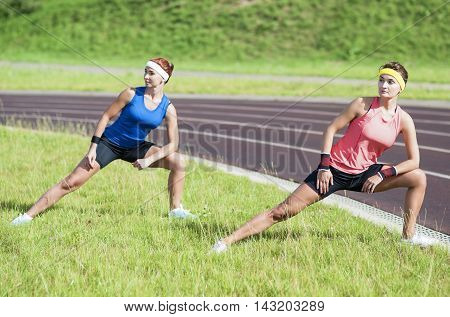 Healthy Lifestyle Ideas and Concepts. Two Young Caucasian Girlfriends in Athletic Sportswear Having Trunk Bending Exercises.Horizontal Orientation