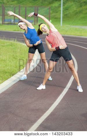 Portrait of Two Young Feale Sportswomen Having Stretching Exercises Outdoors. Vertical Image Composition