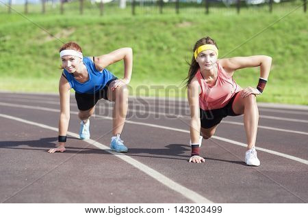 Fitness and Workout Concepts and Ideas. Two Caucasian Girlfriends Having Stretching Exercises On Sport Venue Outdoors. Horizontal Image