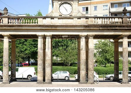An old gate with columns and a clock in the Warsaw Street in Berlin.