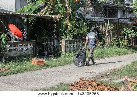 Black garbage bag. man work municipal recycling garbage collector freehand Black. garbage bag The at which danger.