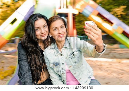 young beautiful women taking selfie outdoor on the carousel
