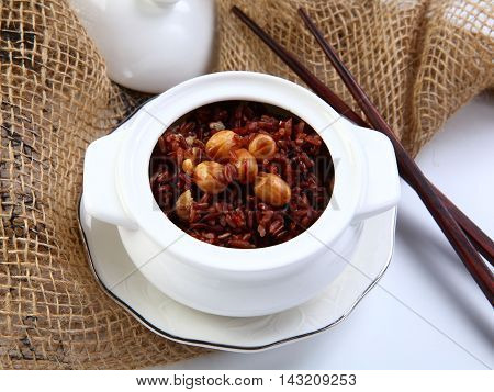 Red sticky rice with lotus bean on white bowl in restaurant