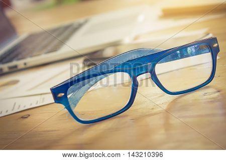 Close up eye glasses on wooden desk. vintage effect.