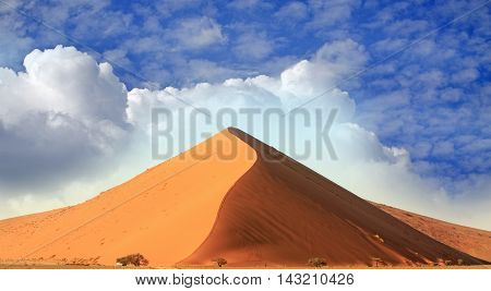 Dune 45 in the Namib Naukluft Desert with visible walking path against a blue cloudy sky background