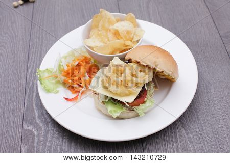 Fried tempura hamburger with fried potatoes and salad on white plate
