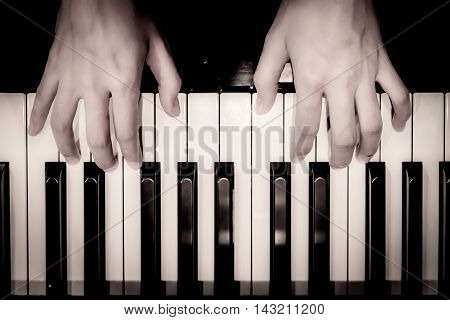 Black & white Hand playing piano.vintage effect.