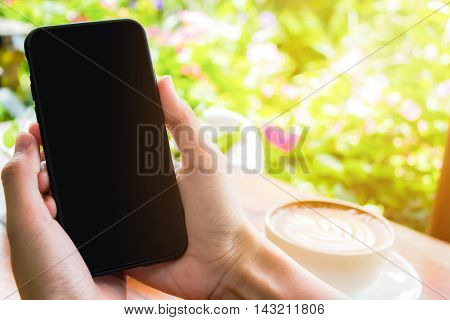 Hand holding smart phone at morning day. Smartphone with blank screen and can be add your texts or others on smart phone.Smart phone concept.