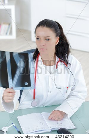 doctor looking at the x-ray picture of hand