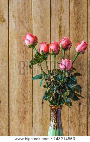 pink roses in vase on wood background