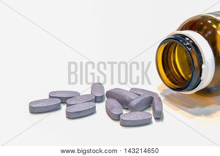 Closeup pills spilled from a bottle on white background.