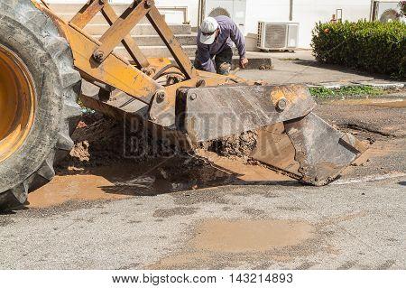 Plumbing Repair Man and excavator scoop digging Repair of pipe water and sewerage on road worker fixing broken water main.