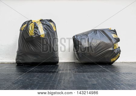 Group of black garbage bags put fully covered with adhesive tape .