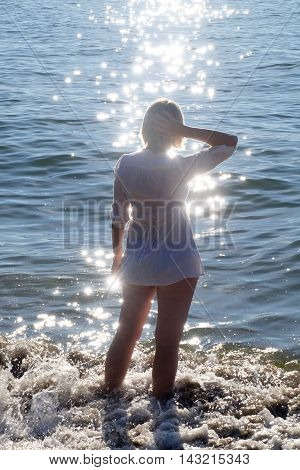 Woman Silhouette On Beach With Glittering Water.