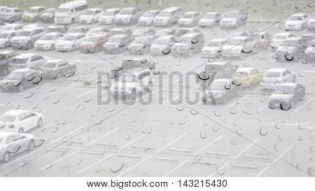 Double exposure of raindrops perched on the glass while it is raining with cars parking.