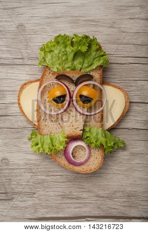 Funny sandwich man made on wooden background