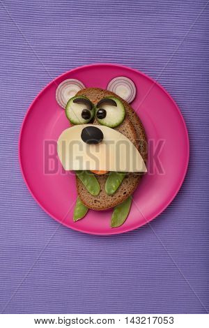 Amusing bear made of bread and vegetables on plate and board