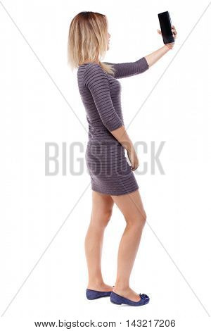 back view of standing young beautiful  woman  using a mobile phone. girl  watching. Rear view people collection.  backside view of person.  Isolated over white background. Blonde in violet short dress