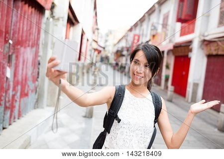 Young Woman taking self image by digital camera in Macao