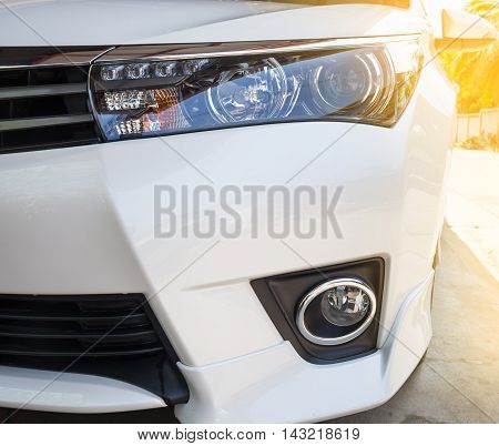 Closeup headlights of modern white car with LED daylight running lights