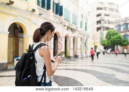 Woman backpacker using mobile phone