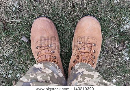 military boots on the colorless dry grass