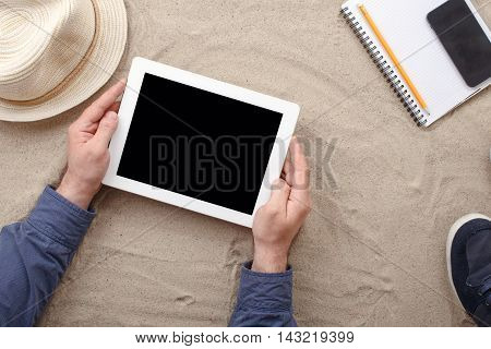 Man holding tablet with blank screen lying on the beach Top view. Man working using tablet computer on the beach. Concept of work outside of the office