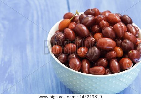 Bowl of fresh cranberries on the wooden background
