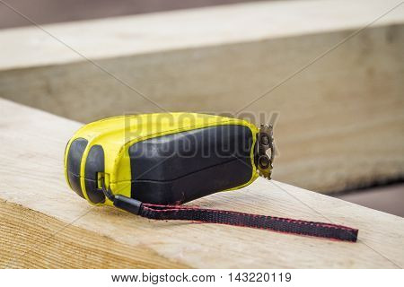 Yellow tape measure lying on a wooden structure