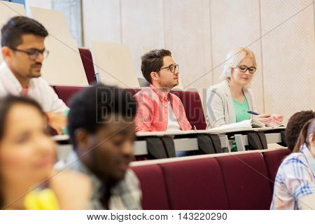 education, high school, university, learning and people concept - group of international students with notebooks in lecture hall and talking