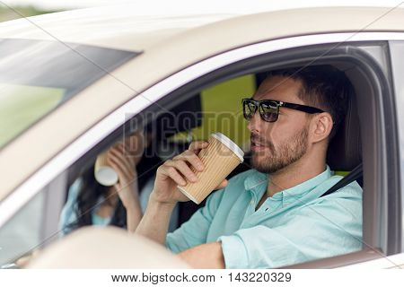 leisure, road trip, travel, family and people concept - happy man and woman driving in car with coffee