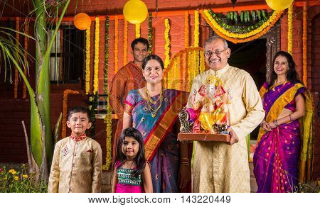 Smart Indian old couple holding Ganesh idol or ganpati idol at entrance, welcoming lord ganesh on ganesh festival or chaturthi with grand childrens and kids in the background, happiness concept