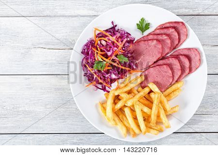 sliced smoked veal fillet french fries and red cabbage salad with carrots meat cherry tomatoes and parsley on white rustic boards view from above