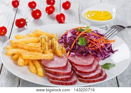 french fries and sliced smoked veal with cabbage salad on white plate on white table with mustard in gravy boat view from above close-up