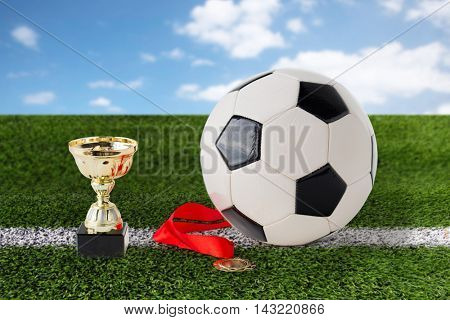 sport, achievement, championship, competition and success concept - close up of football or soccer ball with golden medal and cup over playing field and blue sky background