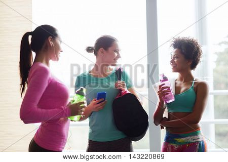fitness, sport, training and lifestyle concept - group of happy women with bottles of water, smartphone and bag talking in gym
