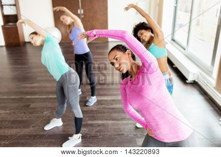 fitness, sport, training, exercising and people concept - group of happy women working out and stretching in gym
