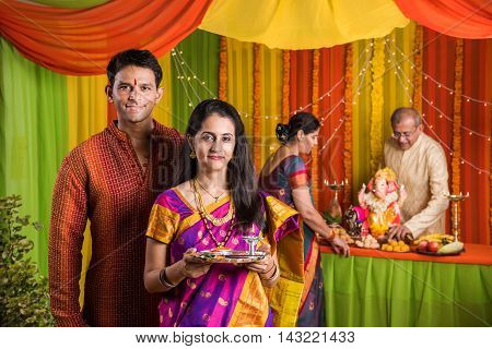 indian young couple with puja thali performing puja on ganesh festival or ganesh utsav