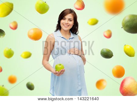 pregnancy, healthy eating, food and people concept - happy pregnant woman holding green apple over green natural background with fruits