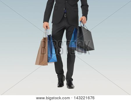 people, sale, fashion and consumerism concept - close up of man in suit with shopping bags over blue background